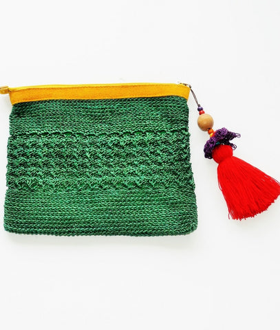 green raffia boho clutch with oversized red tassel and leather trim