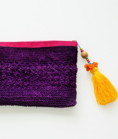 purple raffia boho clutch with oversized orange tassel and leather trim