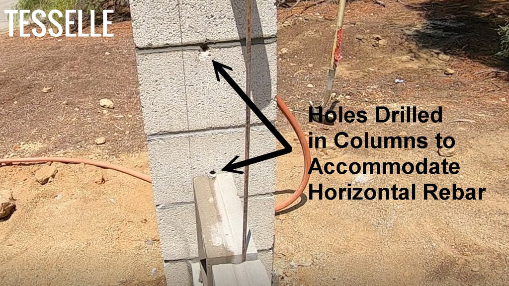Holes drilled in columns to accommodate rebar in breeze block wall