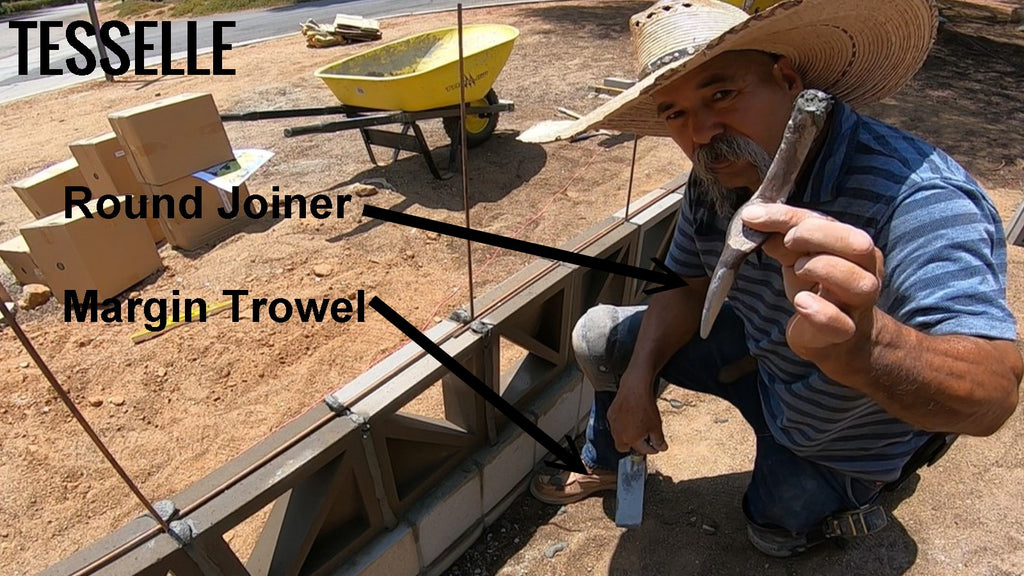 Using a round joiner and margin trowel to build a breeze block wall.