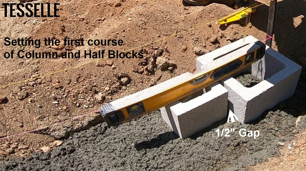 Laying the first course of structural blocks in a garden wall