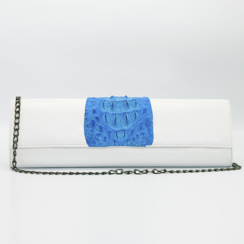 "Blue and white Kate crocodile and leather clutch. Handcrafted from Italian saffino leather. Sustainably sourced crocodile ascent, magnetic closure, interior pocket, and removable shoulder strap with a 22"" drop."