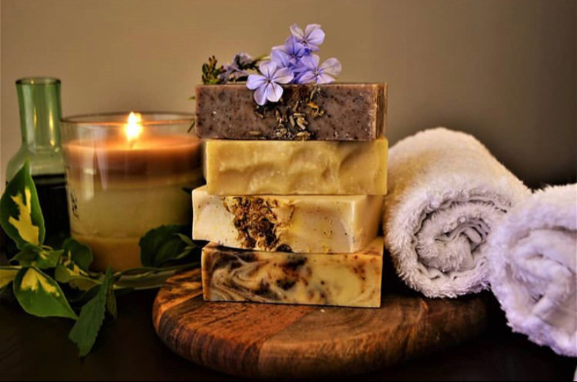 Spa themed picture of 4 luxuriously hand crafted soaps made by YellowBerry with a backdrop of towels and a candle