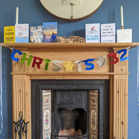 Fireplace decorated with cards and a banner for a lockdown birthday.