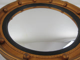 Regency style convex mirror with gilt and ebonised frame