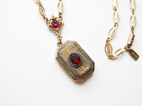 Gold toned locket with red stones by 1928 company