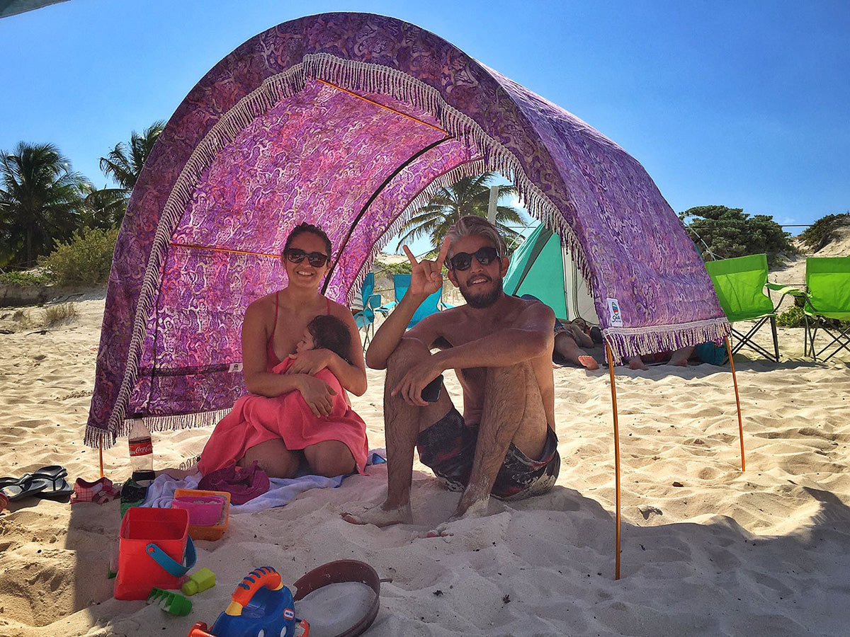 Family sits beneath arched Suniela Beach shade cabana in Mexico