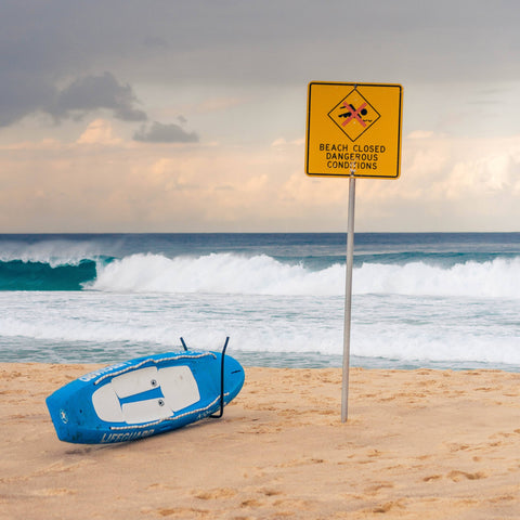 Beach with sign warning of closure due to dangerous conditions