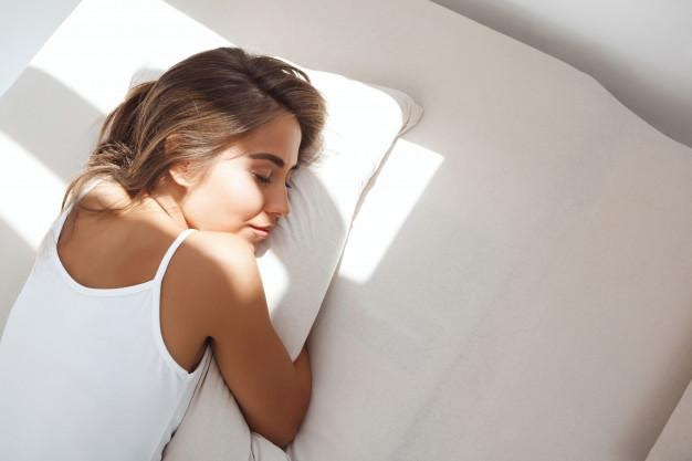 Woman laying on bed with a sunbeam across her face, hugging her pillow