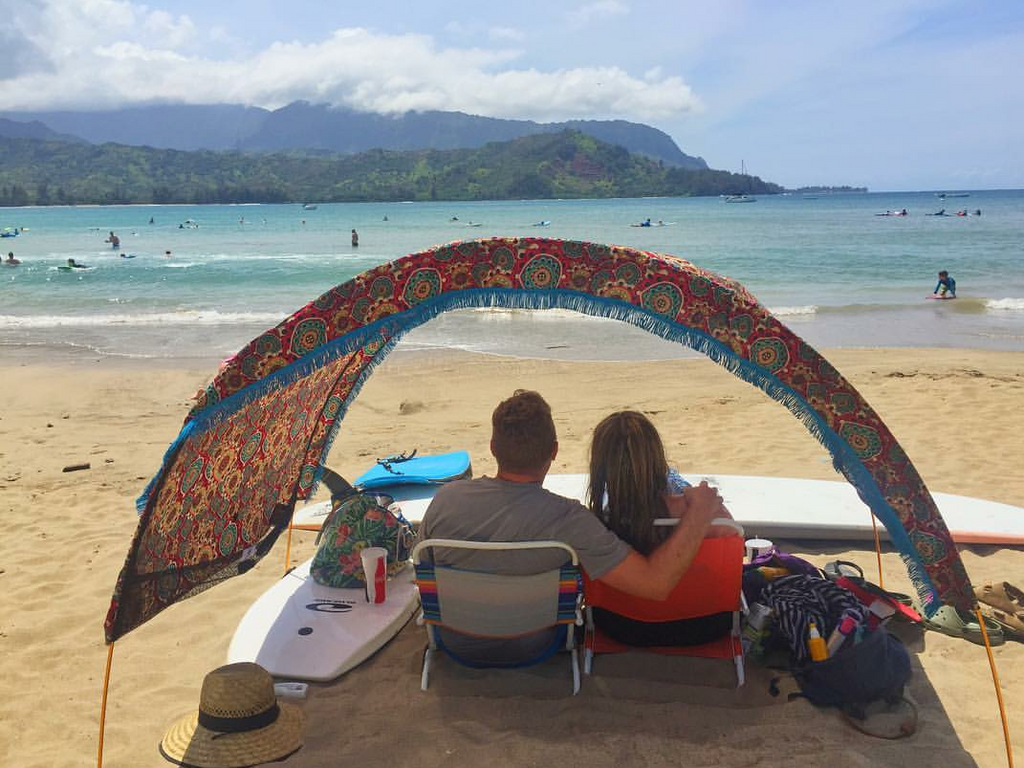 Couple enjoying their Suniela Beach cabana - surfing vacation