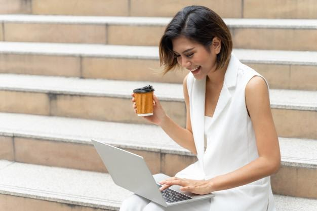 Woman sitting outdoors on steps with laptop on her lap and coffee in hand, smiling