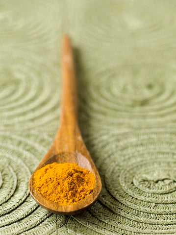 wooden spoon with ground turmeric