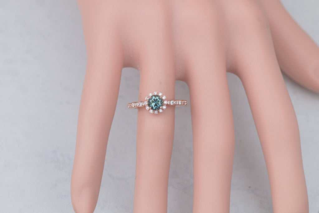rose gold engagement ring with blue green gemstone