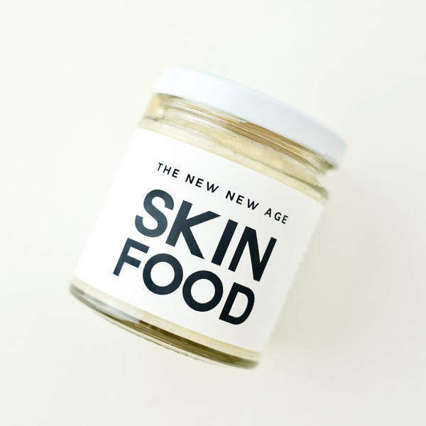 A jar of Skin Food, made of organic virgin coconut oil, raw cacao butter and unrefined, treatment-free beeswax. Formulated by The New New Age.
