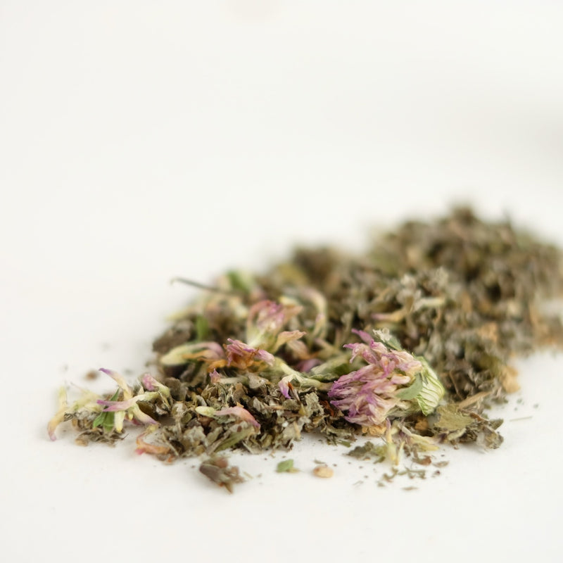 A close up of an organic herbal tea that is a tonifying women's health tonic featuring red raspberry leaf, red clover, and ginger. This tea is called Moon Medicine.