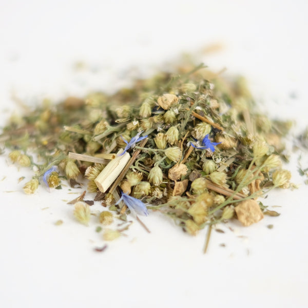 A close up of Wounded Healer. An organic herbal tea formulated by The New New Age, this tea features yarrow, ginger, lemon verbena, lemongrass, lemon balm, blue cornflower, black pepper.