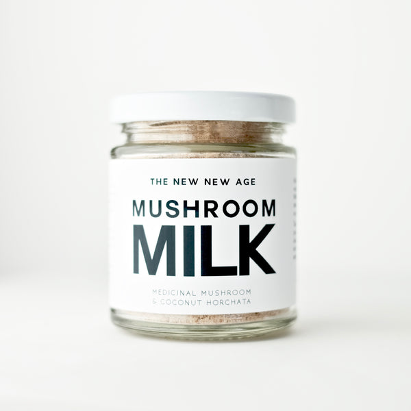 A jar of an organic herbal powder instant beverage, formulated by The New New Age. Mushroom Milk is a delicious blend of dehydrated organic coconut milk and 6 medicinal mushroom extract powders (chaga and reishi dual extract, lions mane, maitake, cordyceps, and turkey tail). Mushroom Milk is a creamy, nourishing instant beverage with immune and adaptogenic support.