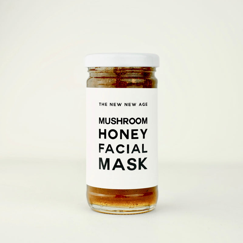 A jar of Mushroom Honey Face Mask by The New New Age. Featuring raw honey, wild foraged chaga mushroom powder, organic reishi and chaga dual extract, organic coriolus extract, organic cordyceps extract, organic lion's mane extract & maitake extract.