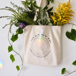 A natural cotton 100% organic tote bag with the words The New New Age, Herb Farm & Nature Sanctuary. There are different organic herbs in the bag, such as holy basil, sage, passionflower, rosemary and golden rod.