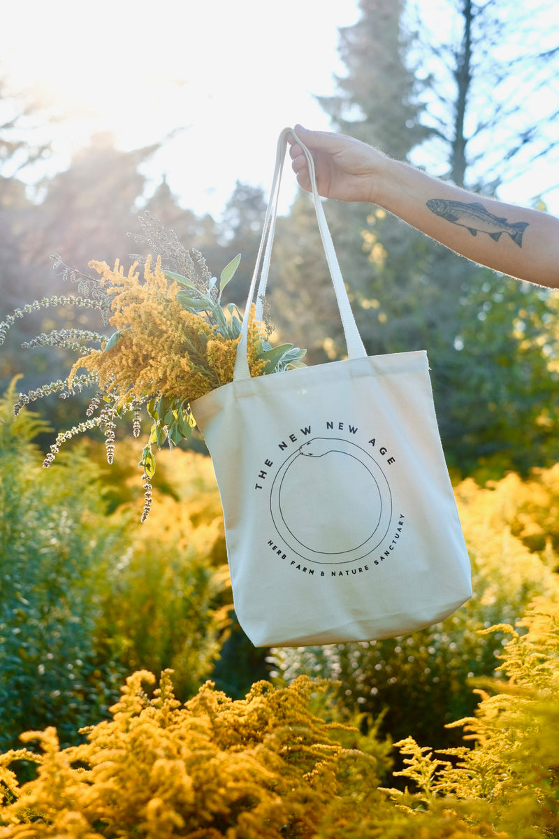 A natural cotton 100% organic tote bag with the words The New New Age, Herb Farm & Nature Sanctuary. Shown here in a field of Goldenrod at The New New Age farm.
