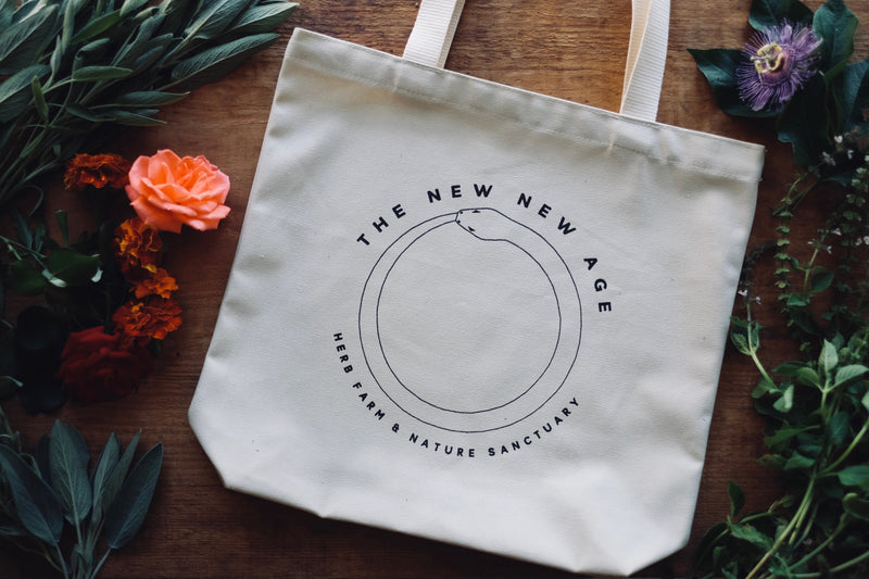 A natural cotton 100% organic tote bag with the words The New New Age, Herb Farm & Nature Sanctuary.