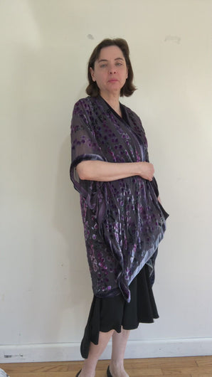 women in video modeling devoré or burnout velvet kimono jacket showing all sides. Duster length jacket  over black dress. The duster style jacket is black sheer chiffon background with an all over pattern of willow branches with purple accents.