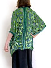 Load image into Gallery viewer, modeling green gingko leaf modeling the back of a  devoré or burnout velvet kimono jacket that is hand painted Gingko Leaves. Worn over back dress.