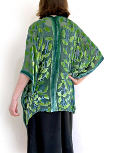 modeling green gingko leaf modeling the back of a  devoré or burnout velvet kimono jacket that is hand painted Gingko Leaves. Worn over back dress.