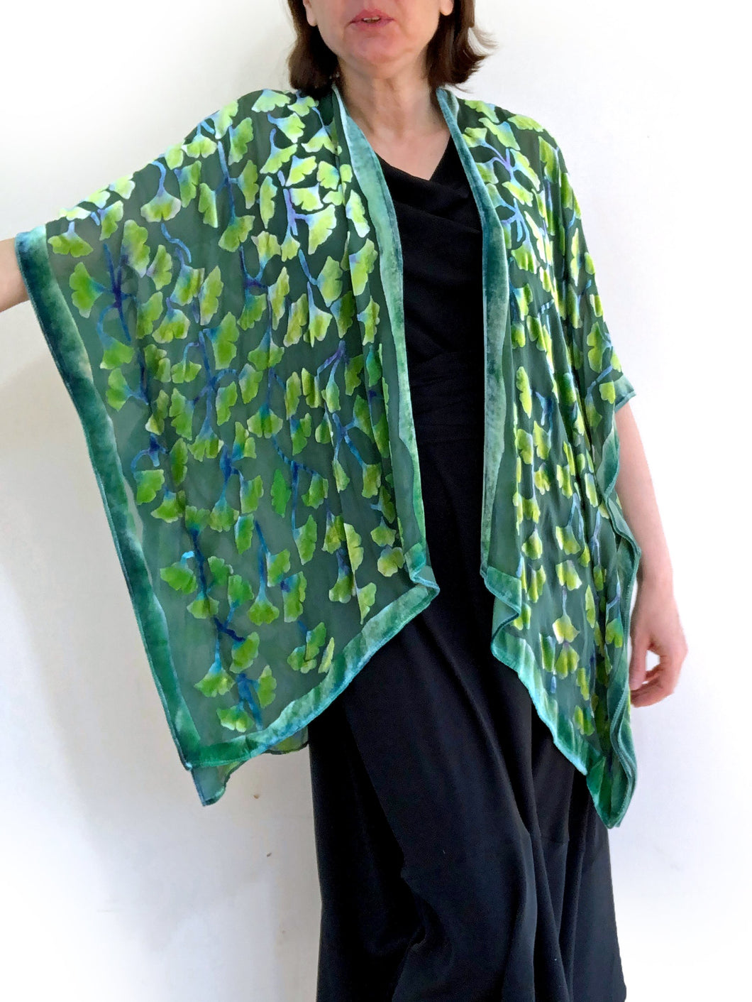 modeling green gingko leaf devoré or burnout velvet kimono jacket that is hand painted. Worn over back dress.