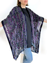 Load image into Gallery viewer, women modeling devoré or burnout velvet kimono jacket holding up arms to show kimono style over black top and jeans.  The duster style jacket is black sheer chiffon background with an all over pattern of willow branches with purple accents