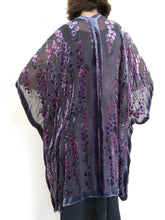Load image into Gallery viewer, women modeling devoré or burnout velvet kimono jacket showing the back. Long duster style over black jeans. The duster style jacket is black sheer chiffon background with an all over pattern of willow branches with purple accents