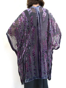 women modeling devoré or burnout velvet kimono jacket showing the back. Long duster style over black jeans. The duster style jacket is black sheer chiffon background with an all over pattern of willow branches with purple accents