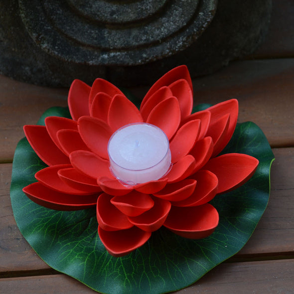 red floating lotus flower with candle