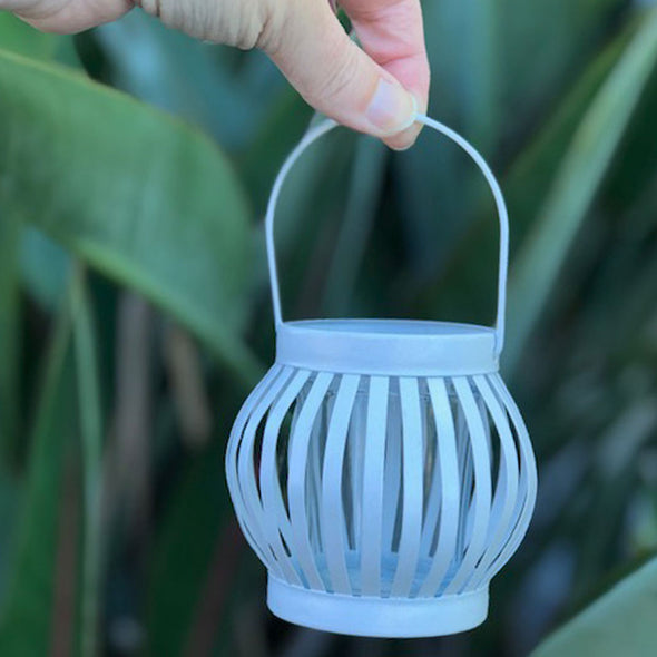 small white metal lantern with candle holder