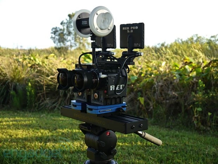 Image of a custom VR capturing rig, including two RED cameras and a 3Dio binaural microphone mounted on a tripod with a corn field in the background.
