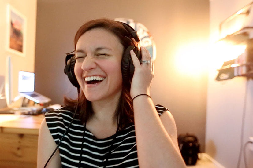 Image of a woman laughing while wearing headphones.