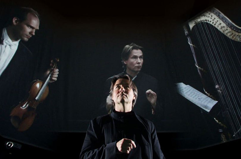 Image of a maestro standing in front of a large projection of musicians.