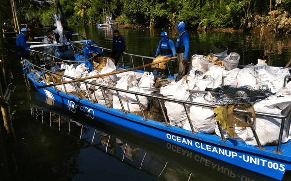 4ocean Employees with Bag of Trash Collected in a Bali River