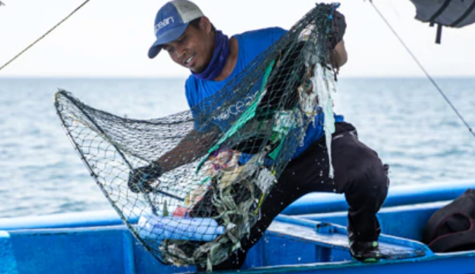 4Ocean crew member pulling trash from the ocean.