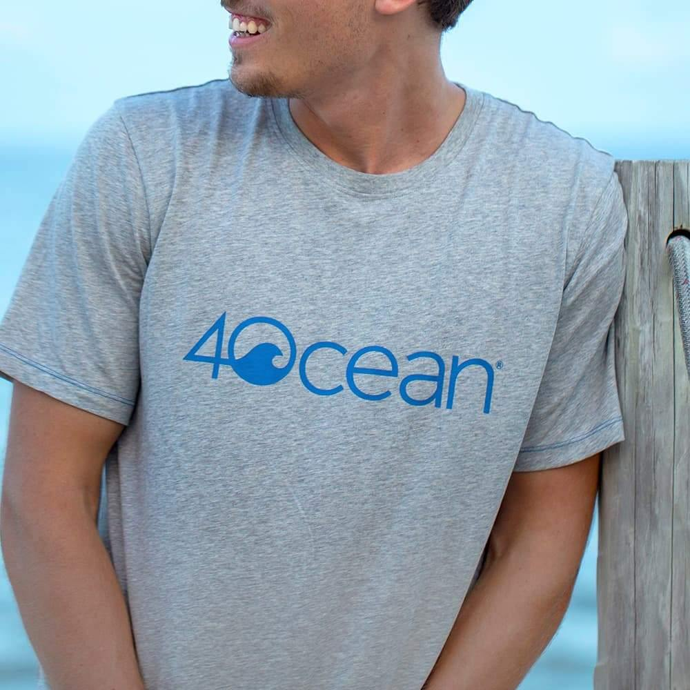 4ocean logo unisex men's and women's t-shirt on a man - grey