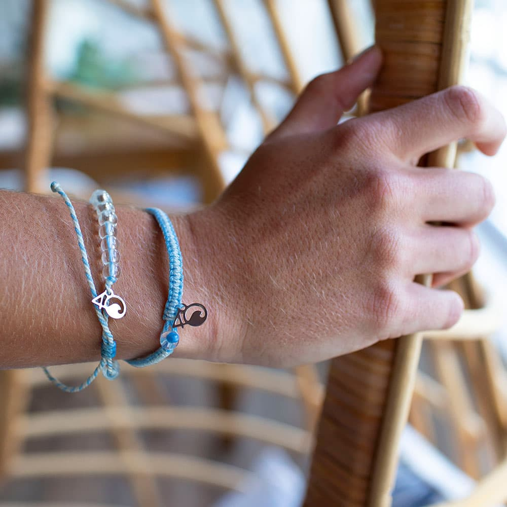 A Person Wearing the 4ocean Beluga Whale Beaded and Braided Bracelet 2-Pound Pack