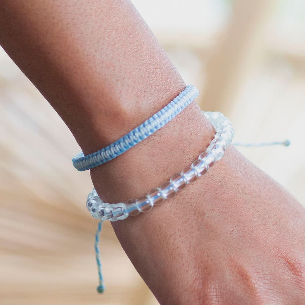 A Closeup of a Person Wearing the 4ocean Beluga Whale Beaded and Braided Bracelet 2-Pound Pack