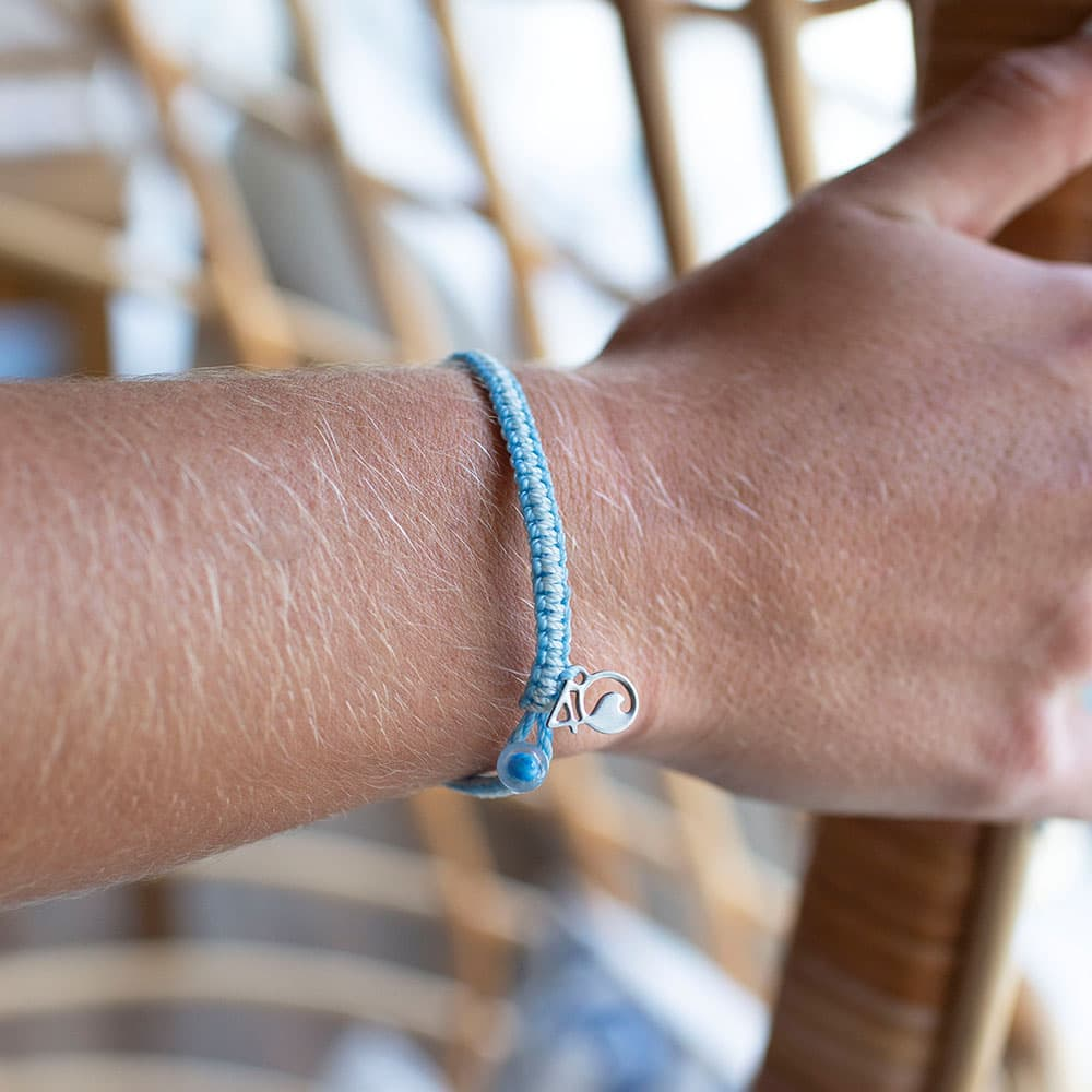 A Closeup of a Person Wearing the 4ocean Beluga Whale Braided Bracelet