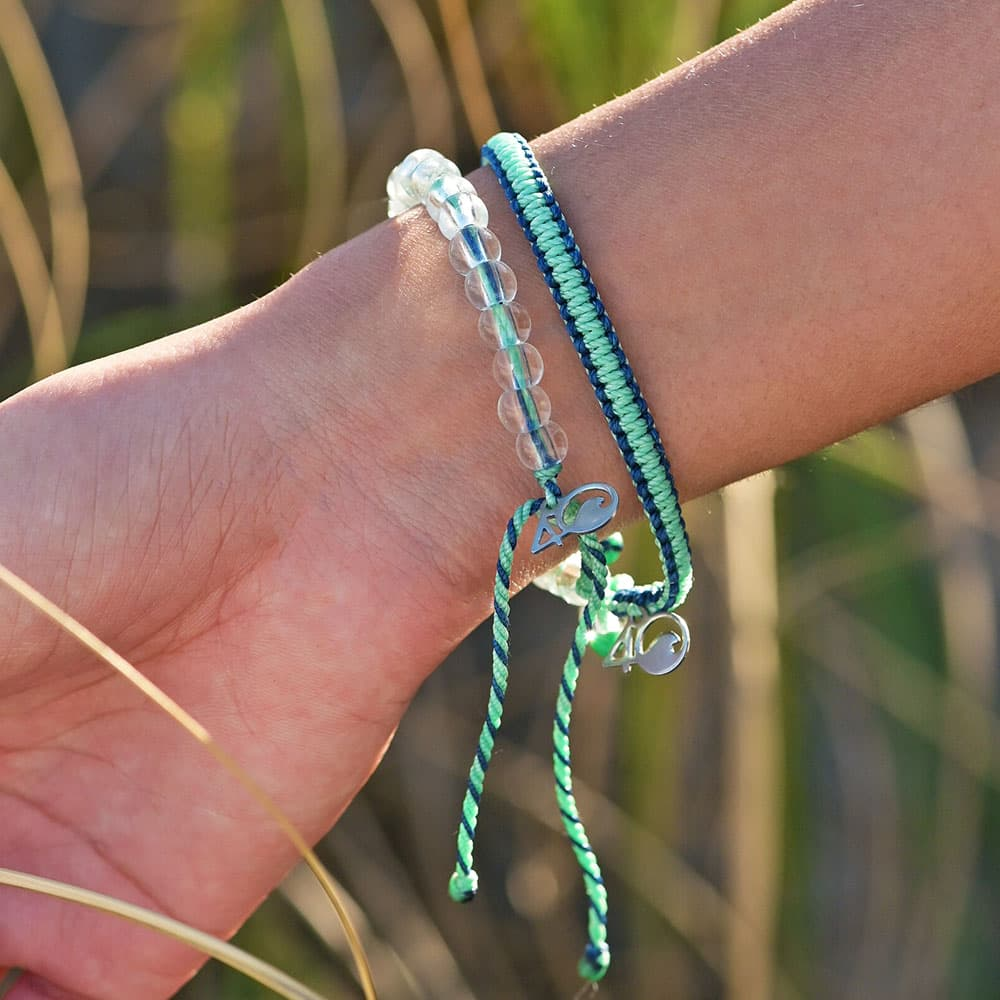 A person wearing the 4ocean Stingray Limited Edition Beaded and Braided Bracelet 2-Pound Pack