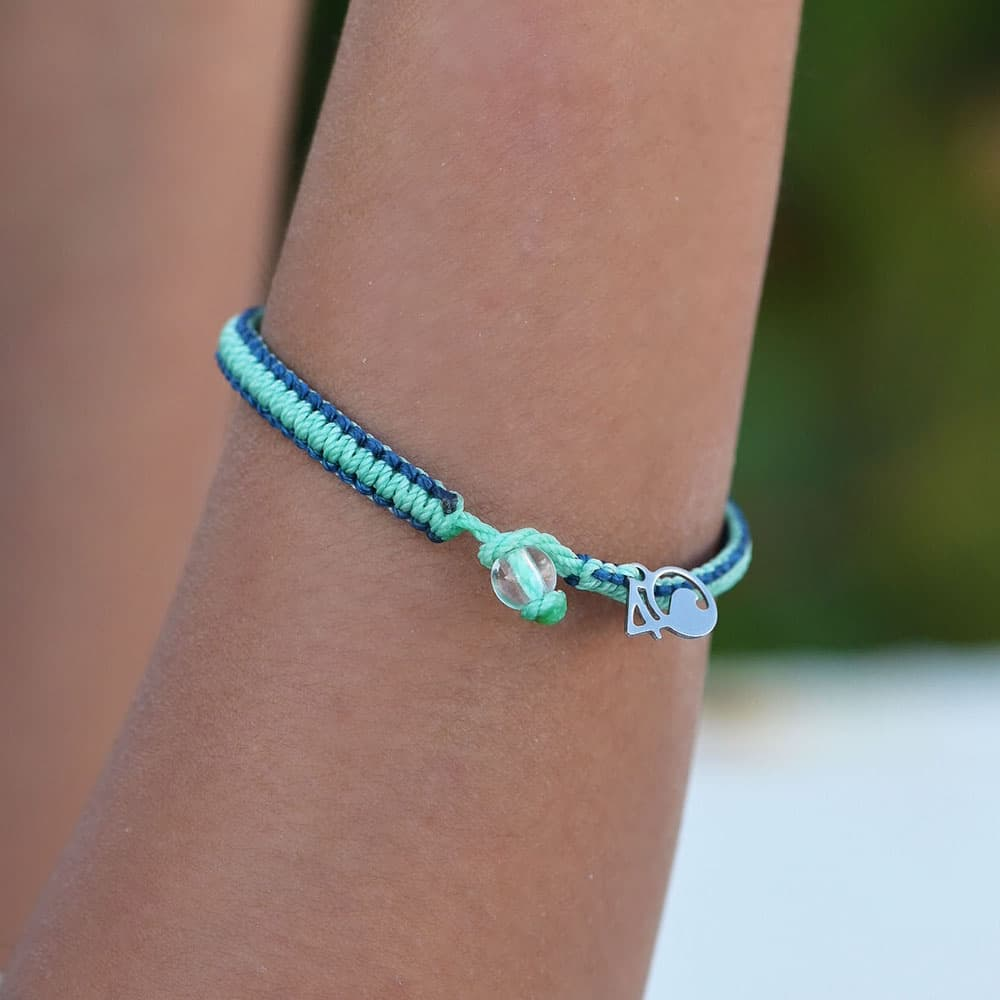 A closeup of a person wearing the 4ocean Stingray Limited Edition Braided Bracelet