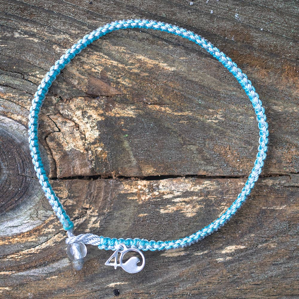 4ocean Dolphin Braided Bracelet on a Wooden Plank