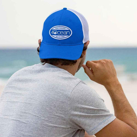 Man wearing the 4ocean surfer badge trucker hat