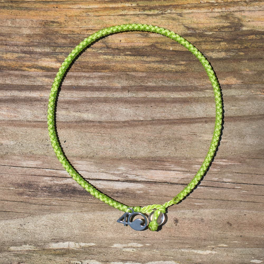 4ocean Sea Turtle Braided Bracelet on a wooden background