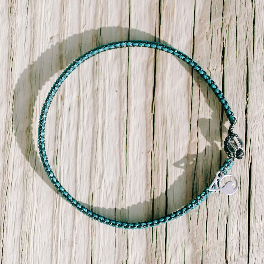 4ocean Sea Otter Braided Bracelet on a Wooden Background