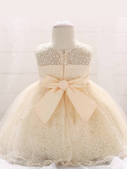 Baby dress has a tulle overlay with embroidered stars with an attached pearl belt and bow at the back-beige